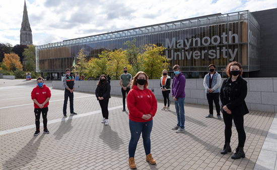 Masked students stand on the sloped walkway to the library from the Kilcock road