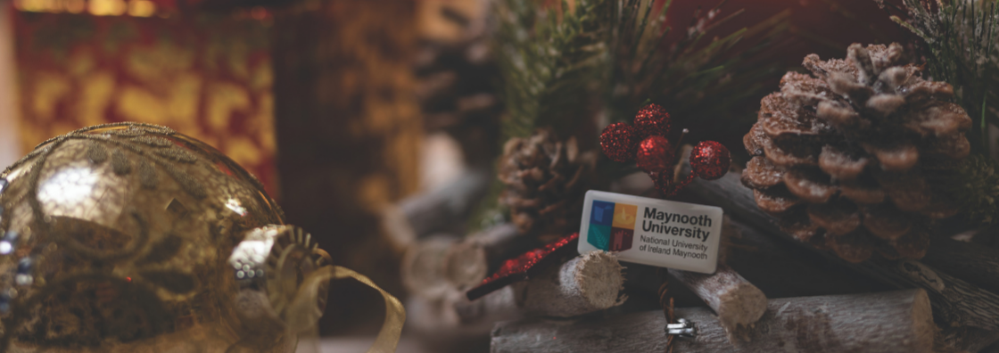 Maynooth University logo enamel pin against a background of Christmas lights and decoration