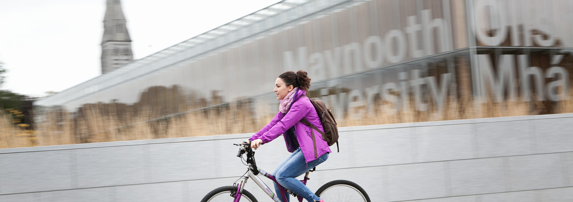 Female cyclist by library sign - Maynooth University