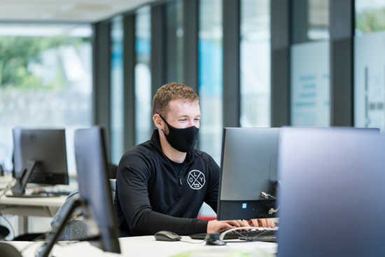 A masked student types on a computer