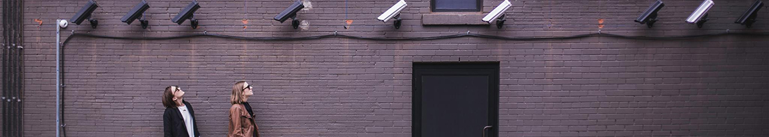People looking up at security cameras - Policy header (Information Security)