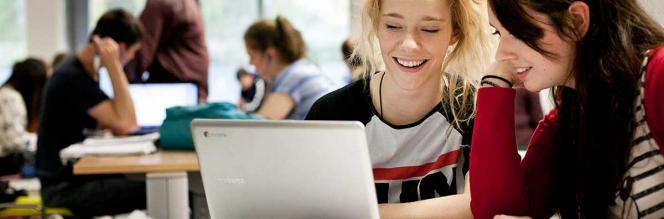 Communications & Marketing - Female students at laptop web 1200 x 396 - Maynooth University