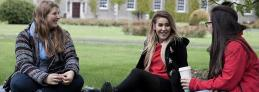 Student Services - Girls sitting on the grass - Maynooth University