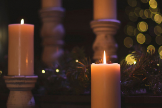 Lit candles against a soft, dark background of pine branches and twinkly lights