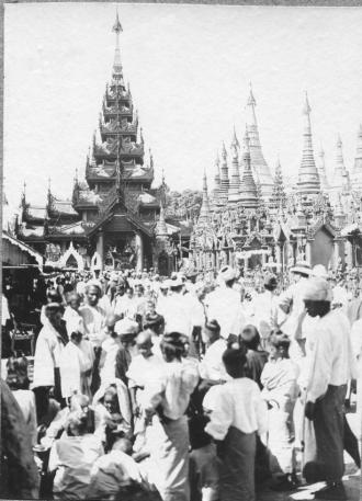 A black & white photograph of devotees outside a temple in Rangoon in the early 1900s.