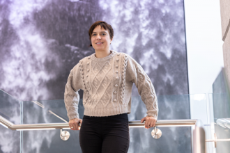 Elisa Fadda faces the camera, standing on a stair landing,  in front of a wall hanging showing flowing water