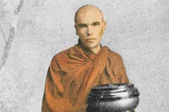 Laurence Carroll in an orange robe, carrying a bowl