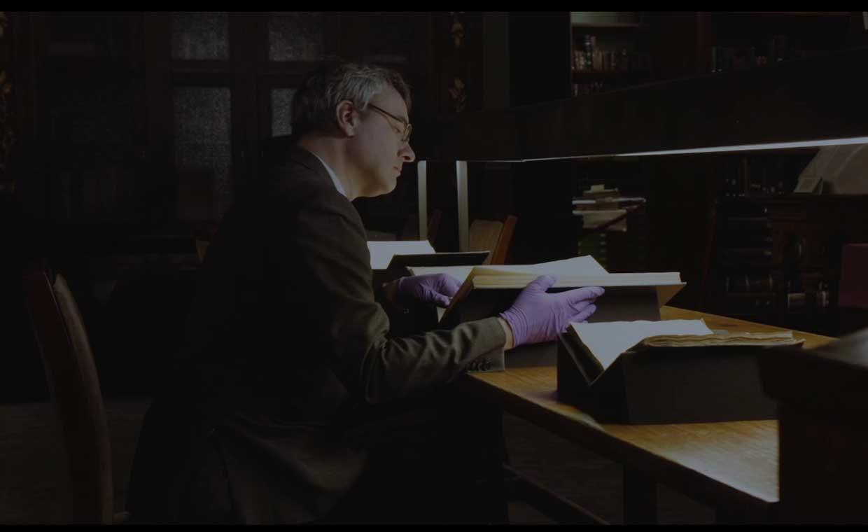 David Stifter, wearing vibrant purple gloves, sits at a bench in the Russel Library and reads a book