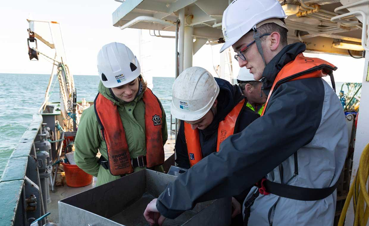 Three research students in white hard hats and life jackets inspecting samples on a boat at sea