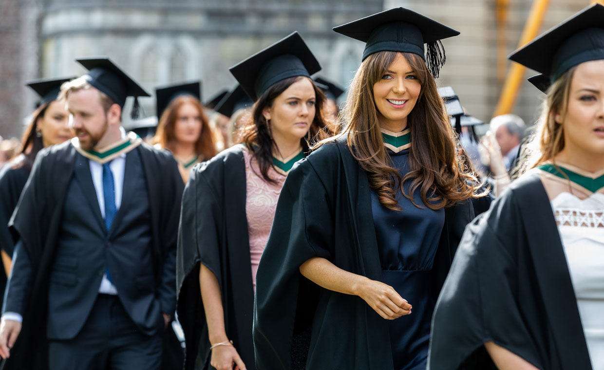 Students in black graduation robes and mortar boards walk towards the aula maxima,