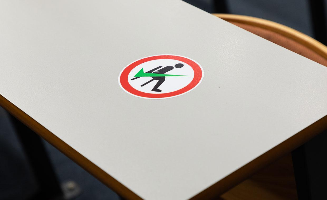 A Social Distancing sticker (Man on black chair, green tick, in a red bound circle) on a desk in John Hume