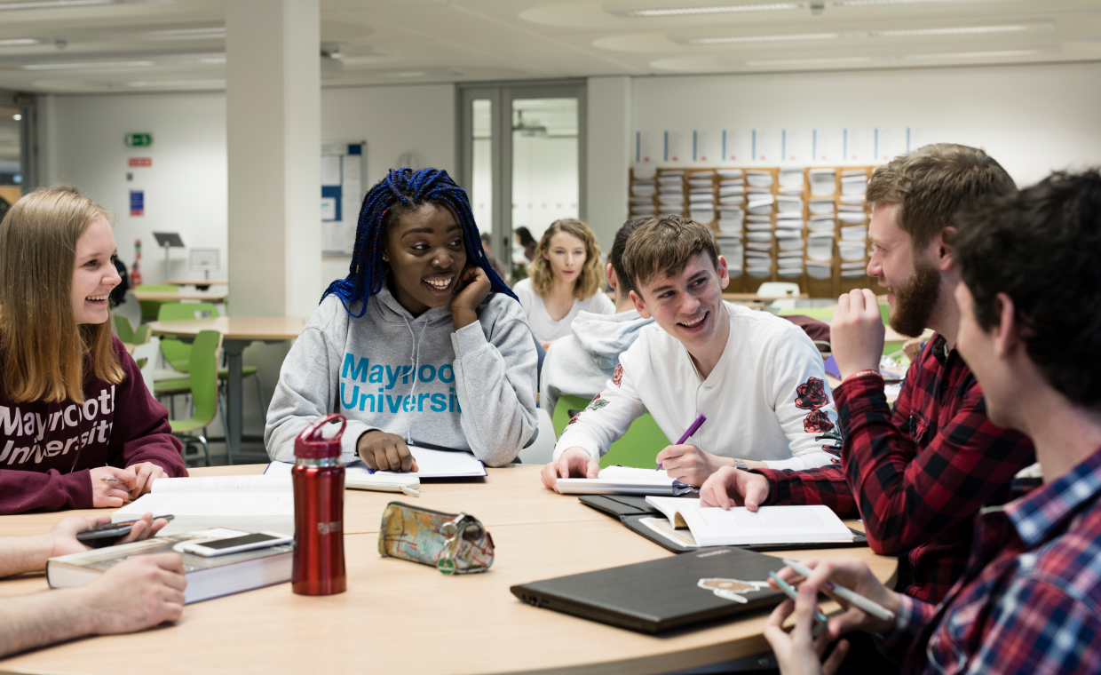 Students wearing Maynooth University hoodies sitting around a table in the library