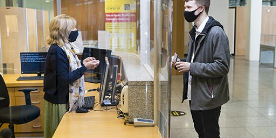 Student in Mask talking to Librarian safely