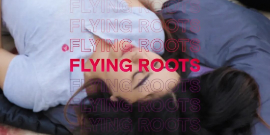 Still image taken from FLying Roots documentary. Shows one of the participants (Teenage girl) with eyes closed with Flying Roots in red in the foreground