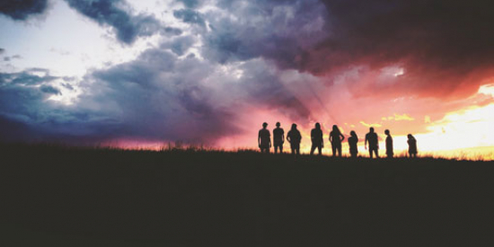 A group of people stand in silhouette against sunrise