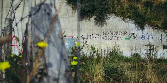 A picture of a wall in an area of wasteland with 'No Borders' spraypainted on it