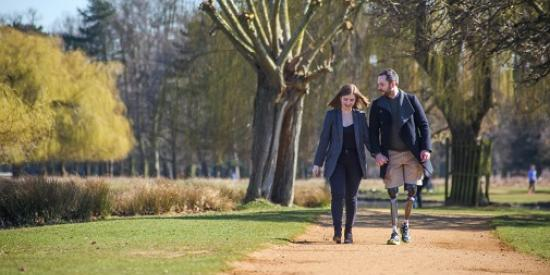 Photo of couple walking in the park, man uses prosthetic leg