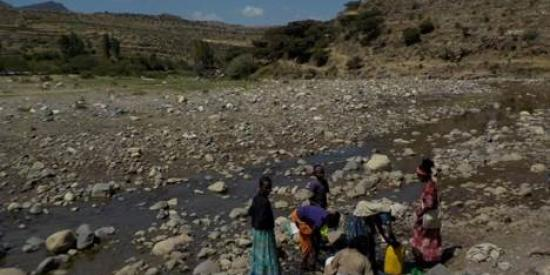 Outskirts of Mekelle, Ethiopia.  Women collecting water for drinking from a drying stream.