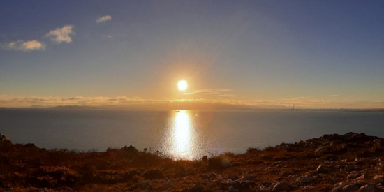 A view out a very calm sea from the land, the sun is setting and its light is stretching in a path across the water