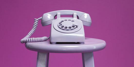 A purple rotary phone on a purple stool against a purple background
