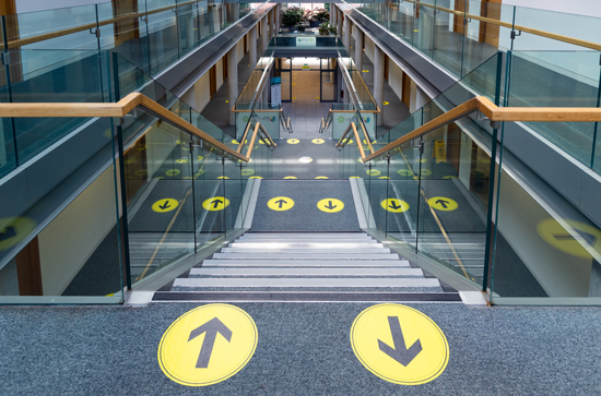 Social distancing signage on the stairs in Iontas showing which side to walk up and down. The stickers are black arrows on yellow circles