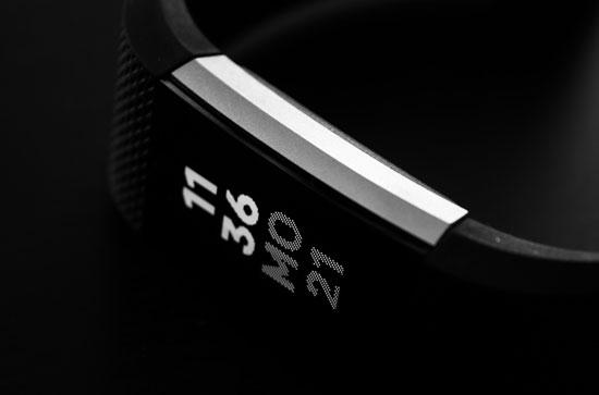 A shot of a fitbit digital screen, all in black and white, against a black background.  The screen reads 11:36, Monday 21